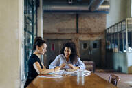 Two young businesswomen talking at conference table in loft office - SODF00355