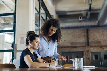 Two young businesswomen talking at conference table in loft office - SODF00358