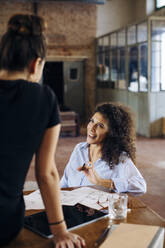 Two young businesswomen talking at table in loft office - SODF00364