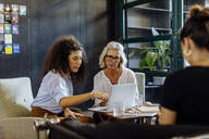 Businesswomen with laptop working together in loft office - SODF00367