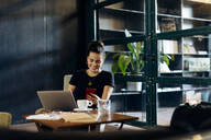 Casual young businesswoman with laptop and smartphone in loft office - SODF00391