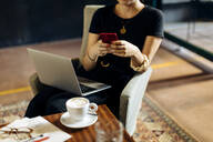 Close-up of young businesswoman with laptop and smartphone in loft office - SODF00394