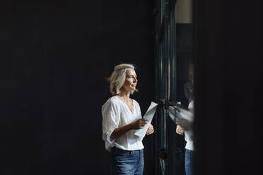 Casual mature businesswoman looking out of window in loft office - SODF00397