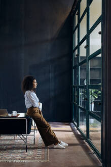Young businesswoman looking out of window in loft office - SODF00406