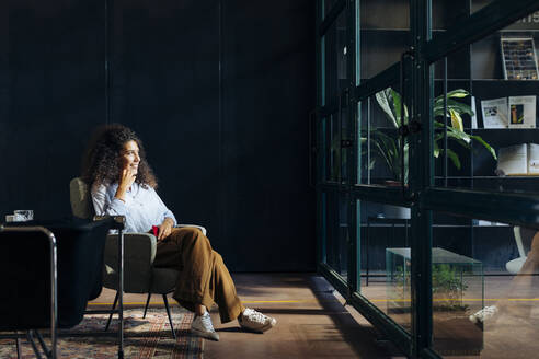 Casual young businesswoman looking out of window in loft office - SODF00409