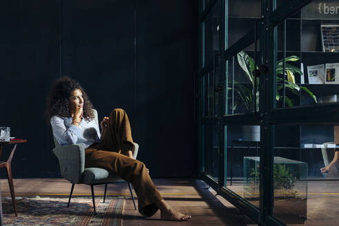 Young businesswoman looking out of window in loft office - SODF00412