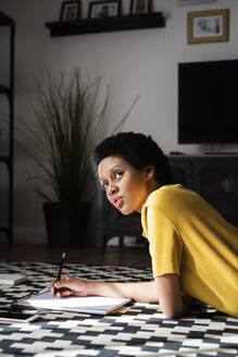 Young woman lying on the floor at home taking notes - GIOF07784