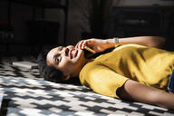 Young woman lying on the floor at home talking on the phone - GIOF07787