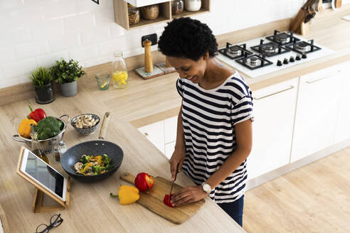 Young woman with tablet cooking in kitchen at home cutting vegetables - GIOF07790