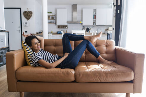 Relaxed young woman lying on couch at home - GIOF07793