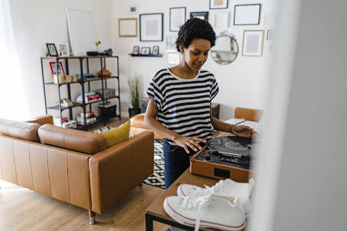 Young woman using record player at home - GIOF07799