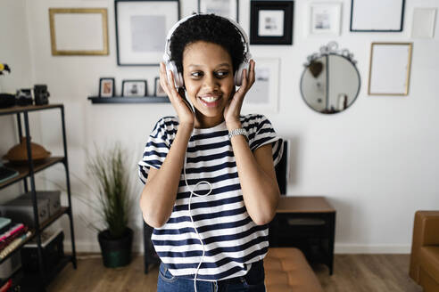 Happy young woman listening to music with headphones at home - GIOF07802