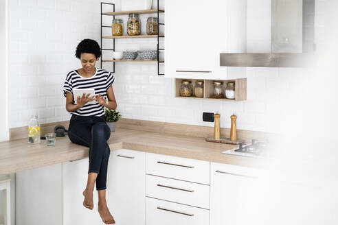 Young woman using tablet in kitchen at home - GIOF07808