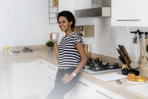 Portrait of smiling young woman holding mug in kitchen at home - GIOF07811