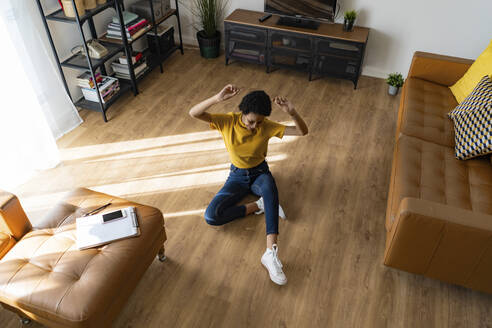 Excited young woman sitting on the floor at home - GIOF07829