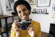 Portait of smiling young woman with vintage camera at home - GIOF07832