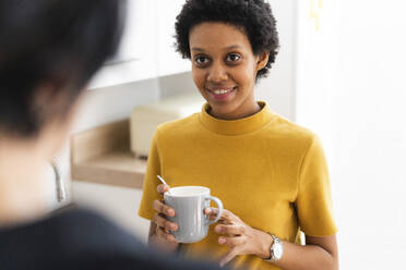 Young woman holding mug meeting friend at home - GIOF07835