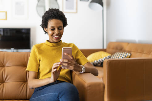 Smiling young woman sitting on couch at home using smartphone - GIOF07838