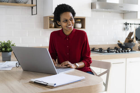 Smiling young woman using laptop at home - GIOF07847