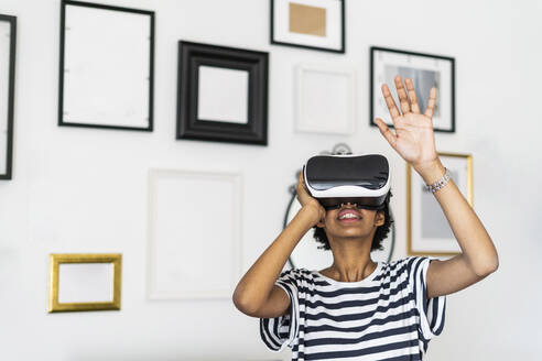 Young woman with VR glasses at home - GIOF07859