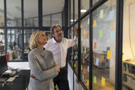 Colleagues looking at sticky notes at glass pane in office - GUSF02686