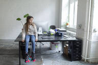 Girl with roller skates sitting on desk in office - GUSF02692