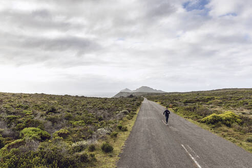 Man jogging on country road, Cape Point, Western Cape, South Africa - MCF00325