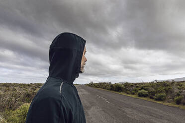 Man in rural scene wearing hooded jacket looking at distance, Cape Point, Western Cape, South Africa - MCF00328