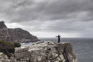 Man standing on rocky cliff looking at horizon, Cape Point, Western Cape, South Africa - MCF00331