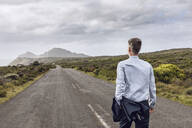 Back view of businessman walking on country road, Cape Point, Western Cape, South Africa - MCF00337
