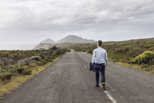Back view of businessman walking on country road, Cape Point, Western Cape, South Africa - MCF00340