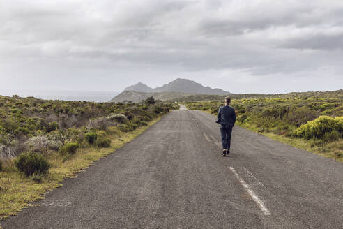 Back view of businessman walking on country road, Cape Point, Western Cape, South Africa - MCF00343