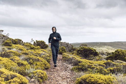 Man jogging in rural scene, Cape Point, Western Cape, South Africa - MCF00346