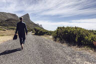 Back view of businessman walking barefoot on country road, Cape Point, Western Cape, South Africa - MCF00349