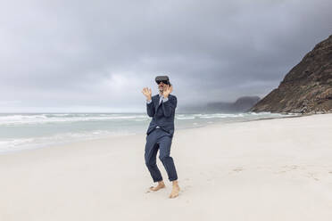 Businessman using VR glasses on the beach, Nordhoek, Western Cape, South Africa - MCF00352