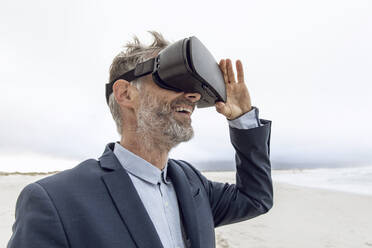 Smiling businessman using VR glasses on the beach, Nordhoek, Western Cape, South Africa - MCF00355