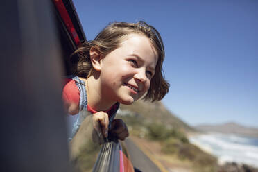Portrait of smiling girl looking out of car window, Cape Town, Western Cape, South Africa - MCF00361