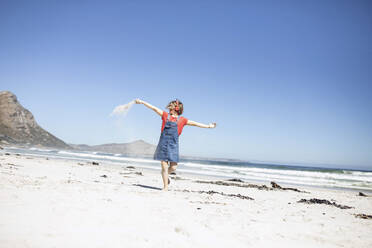 Girl listening music with headphones, dancing on the beach, Cape Town, Western Cape, South Africa - MCF00364