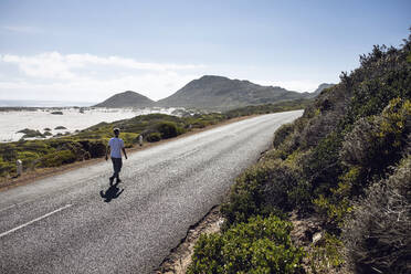 Back view of man walking on country road, Cape Town, Western Cape, South Africa - MCF00376