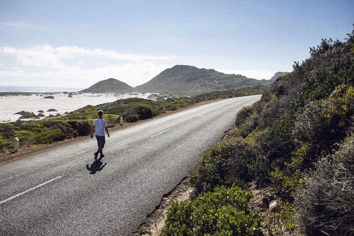 Back view of man walking on country road, Cape Town, Western Cape, South Africa - MCF00376 - Maya Claussen/Westend61