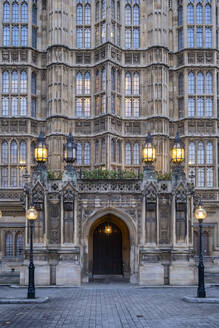 UK, England, London,Street lights glowing in front ofPalace of Westminster entrance at dusk - LOMF00917