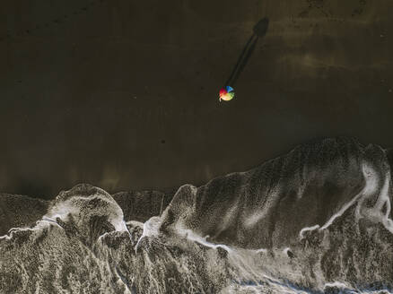 Aerial view of couple unde rainbow colors umbrella at the beach, Kedungu beach, Bali, Indonesia - KNTF03729