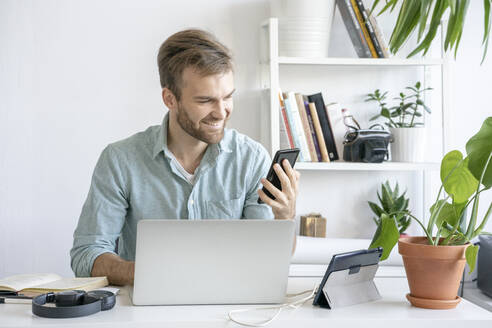 Smiling man using smartphone at desk in office - VPIF01755
