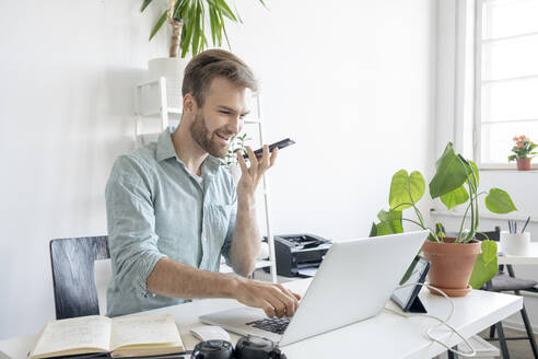Smiling man using smartphone and laptop at desk in office - VPIF01758