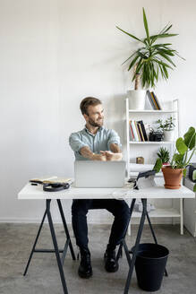 Smiling man at desk in office looking sideways - VPIF01761