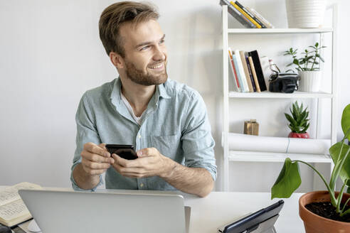 Smiling man using smartphone at desk in office looking sideways - VPIF01764