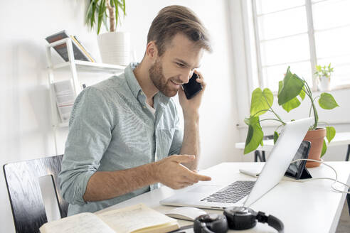 Smiling man on the phone at desk in office - VPIF01767