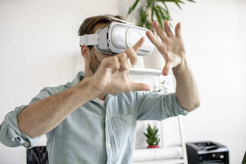 Portrait of man wearing VR glasses in office - VPIF01770