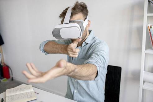 Man wearing VR glasses at desk in office - VPIF01773
