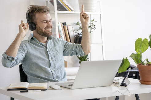 Excited man listening to music at desk in office - VPIF01776